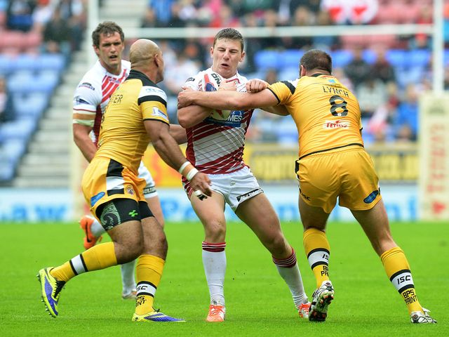 George Williams is tackled by Jake Webster and Andy Lynch