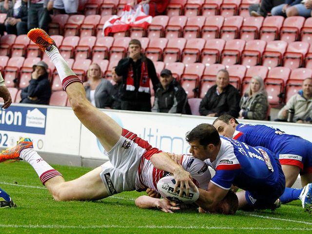 Wigan's Joe Burgess is held up short of the line