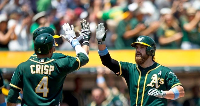 Derek Norris is congratulated by Coco Crisp and Craig Gentry after hitting a three-run home run