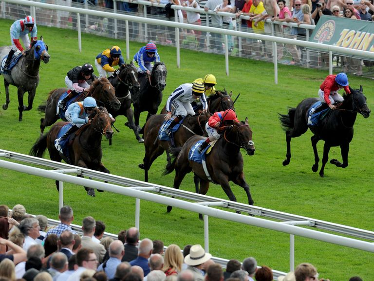 Take Cover ridden by Andrea Atzeni (centre, red silks) wins the John Smith's City Walls Stakes.