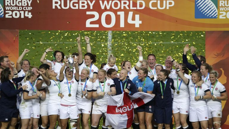 England's players celebrate with the trophy after winning the IRB Women's Rugby World Cup final