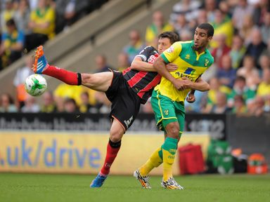 Norwich City's Lewis Grabban (right) is challenged by Bournemouth's Tommy Elphick