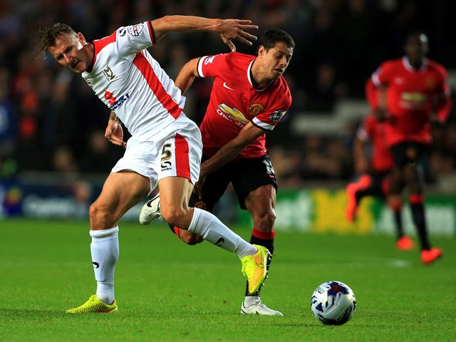 MK Dons' Antony Kay tussles with Manchester United's Javier Hernandez