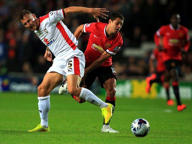MK Dons' Antony Kay tussles with Manchester United's Javier Hernandez