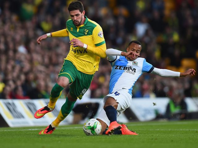 Kyle Lafferty of Norwich City battles with Marcus Olsson of Blackburn