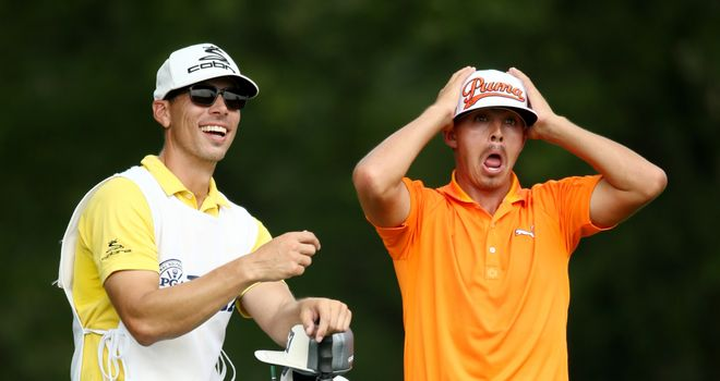 Rickie Fowler (R) of the United States reacts on the fifth tee as caddie Joseph Skovron (L) looks on during the final round of the PGA Championship