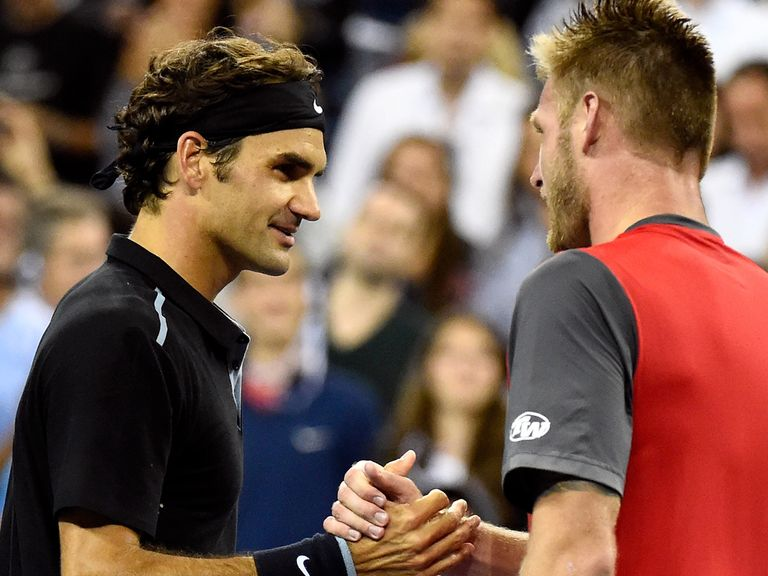 Roger Federer of Switzerland shakes hands with Sam Groth of Australia