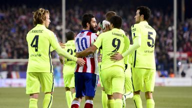 Atletico Madrid's midfielder Arda Turan argues with Barcelona's Uruguayan forward Luis Suarez