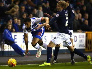 Nick Blackman of Reading skips a tackle from Millwall's Dan Harding