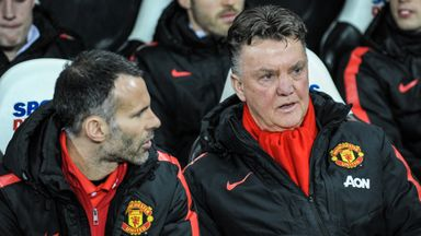 Manchester United manager Louis Van Gaal (R) sits in the dugout with assistant manager Ryan Giggs (L)
