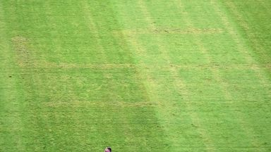 A man looks at the pitch appearing to show the pattern of a swastika