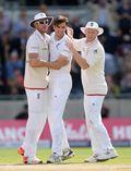 Steven Finn celebrates with team-mates Stuart Broad and Ben Stokes