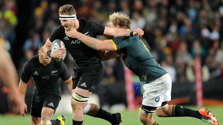 Kieran Read looks to offload as he is tackled by Schalk Burger