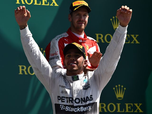 Lewis Hamilton raises his hands as he celebrates on the podium after winning the British Grand Prix