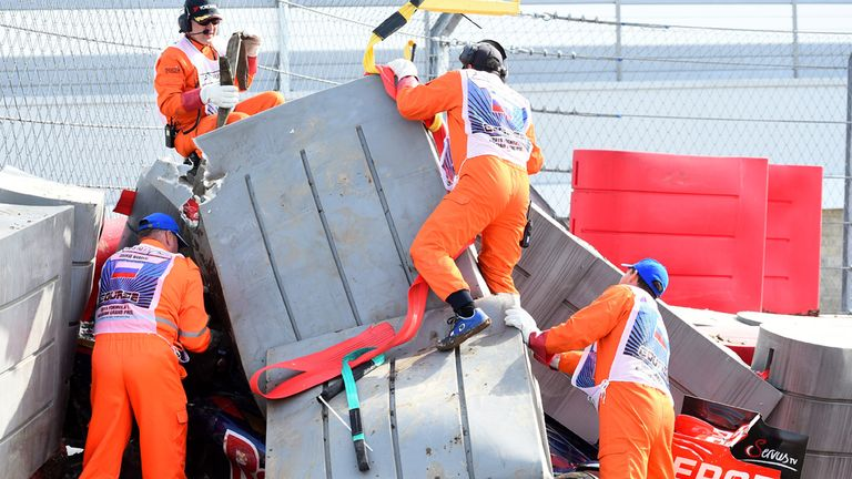 Marshals remove barriers from the top of Carlos Sainz's crashed car