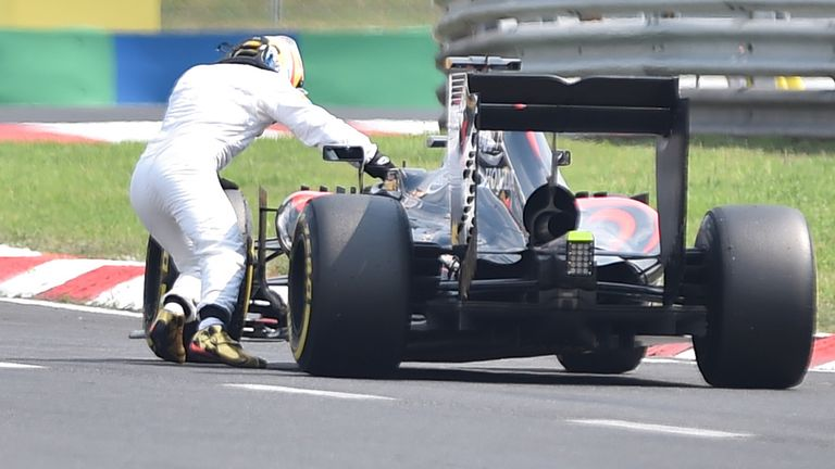 A difficult 2015: Alonso pushes his McLaren back to the pits during qualifying in Hungary