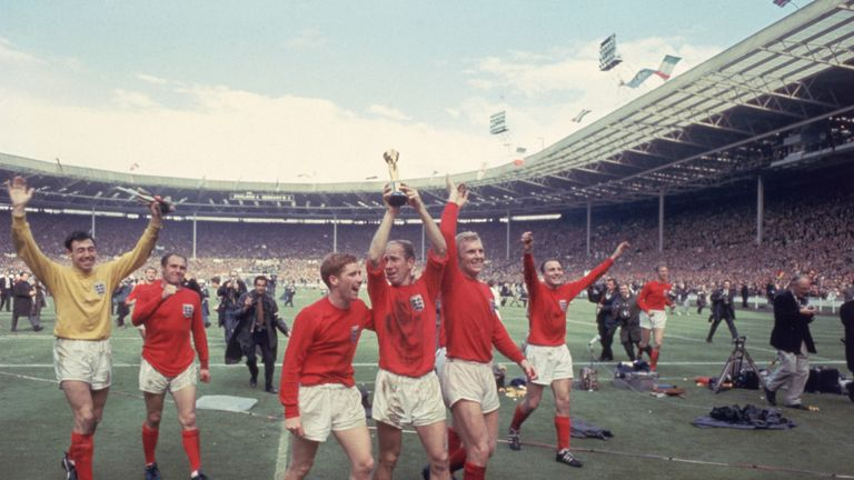 Bobby Charlton (with Alan Ball) raises the Jules Rimet trophy following England's win over West Germany in the World Cup Final at Wembley