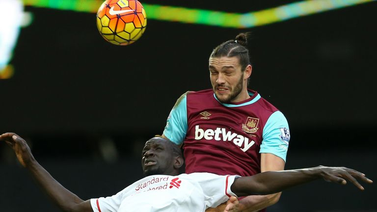 Carroll wins a header against Liverpool's Mamadou Sakho