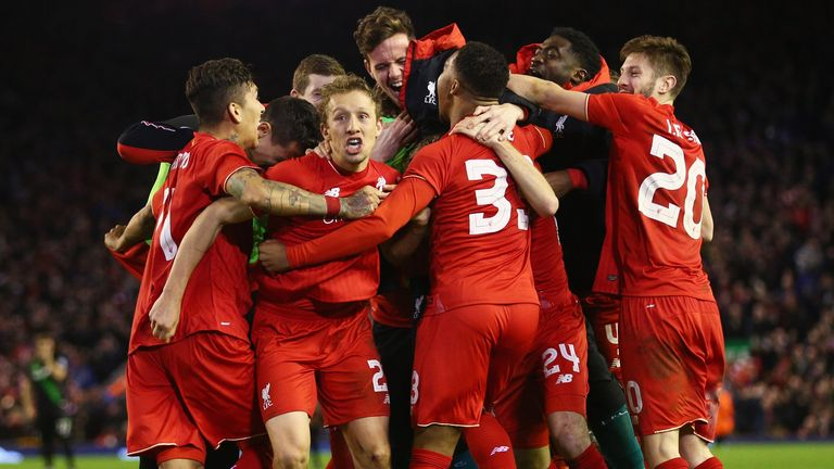 Joe Allen is congratulated by team-mates after scoring the winning penalty for Liverpool against Stoke