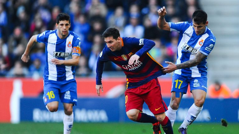 Lionel Messi of FC Barcelona competes for the ball with Hernan Perez (R) and Javi Lopez of RCD Espanyol