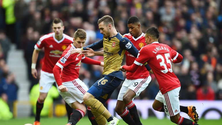 Aaron Ramsey of Arsenal is closed down by Rashford and Jesse Lingard