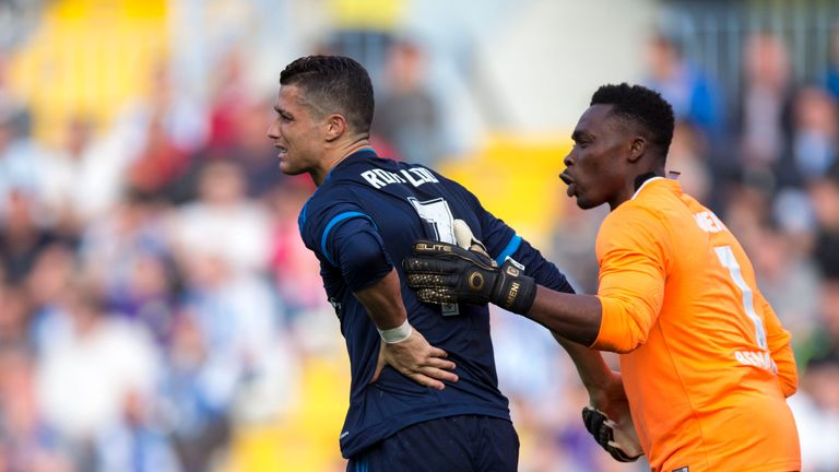 Cristiano Ronaldo grimaces as he is aided by Malaga's Carlos Kameni
