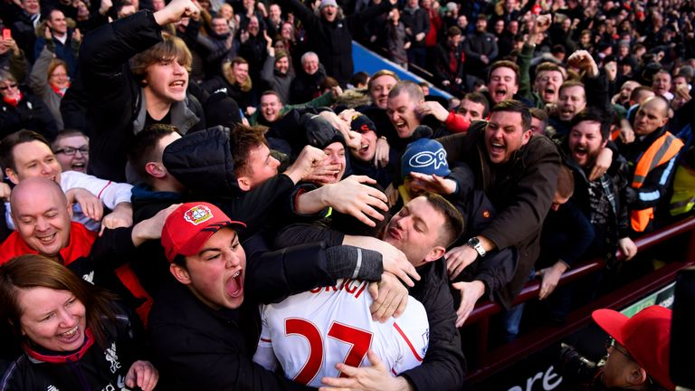 Divock Origi is mobbed by Liverpool fans after scoring.