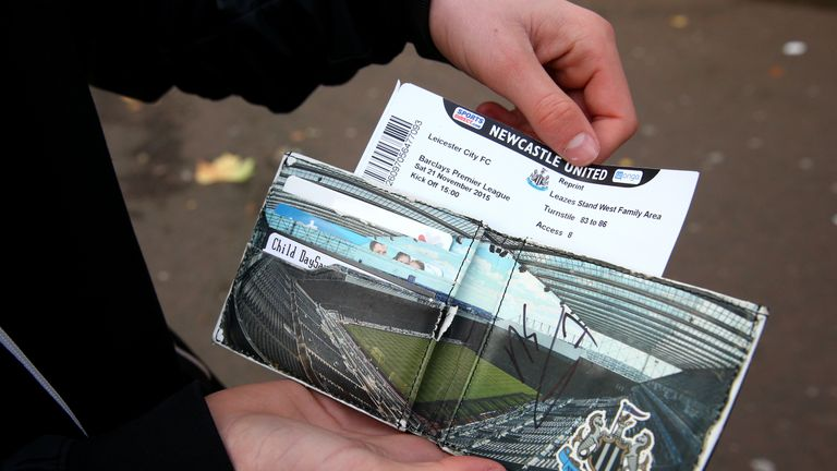 A Newcastle United fans shows his match ticket as he removes it from his NUFC wallet