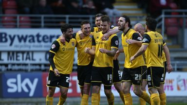 Northampton players celebrate one of James Collins' goals as they stayed top of League Two by thrashing Leyton Orient
