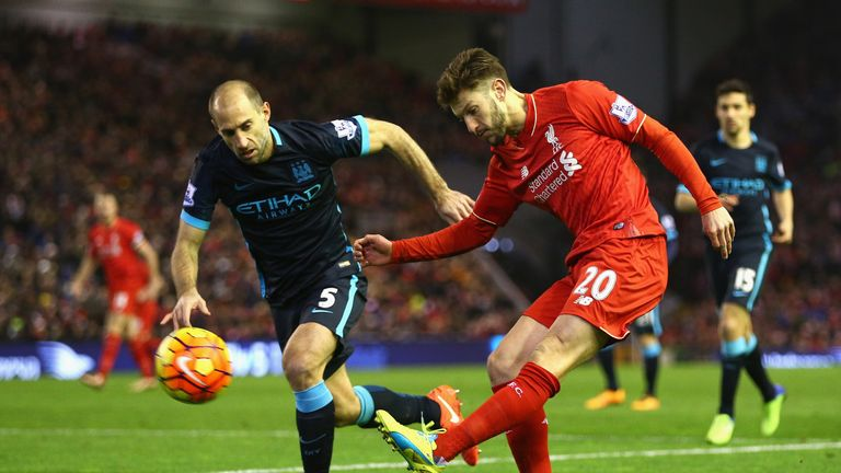 Adam Lallana (right) crosses the ball under pressure