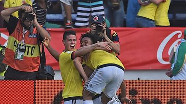 Colombia's Carlos Bacca (back to camera) celebrates with teammates James Rodriguez (L) and Juan Cuadrado after scoring against Ecuador