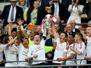 Wayne Rooney and Michael Carrick of Manchester United lift the trophy