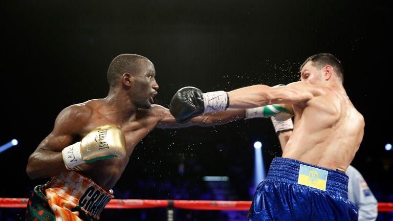 Terence Crawford (L) punches Viktor Postol