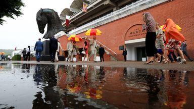 Racegoers reflected in a puddle at a soggy Goodwood