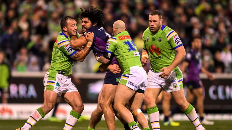 Tohu Harris is tackled by Canberra duo Josh Hodgson (left) and Kurt Baptiste