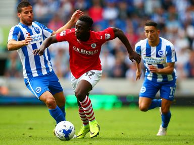 Andy Yiadom of Barnsley battles for the ball with Tomer Hemed and Anthony Knockaert of Brighton