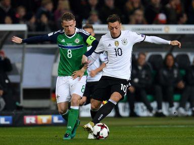 Mesut Ozil tries to get away from Steven Davis