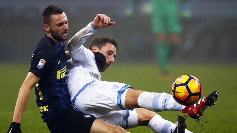 Inter Milan midfielder Marcelo Brozovic (left) fights for the ball with Lucas Biglia