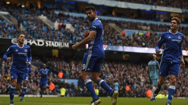 Chelsea's Brazilian-born Spanish striker Diego Costa points to his black armband as he celebrates scoring his team's first goal during the English Premier