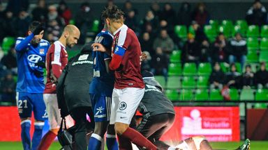 A firecracker explodes beside Lyon and Metz players during the Ligue 1 match on Saturday