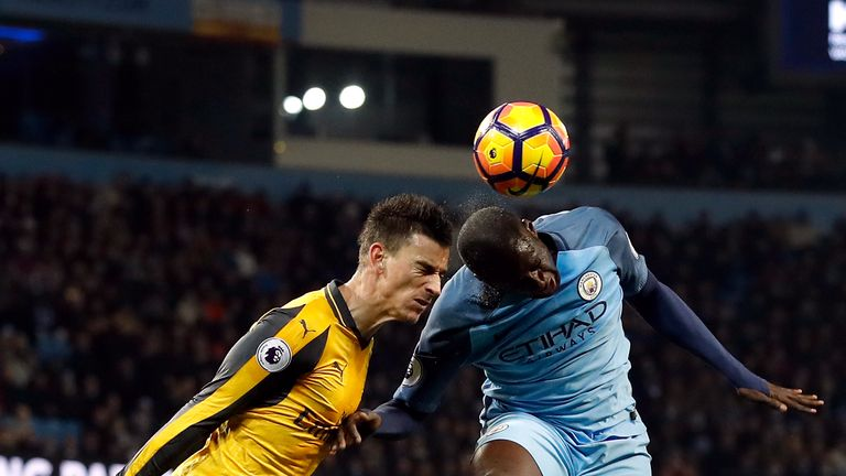 Arsenal's Laurent Koscielny (left) and Manchester City's Yaya Toure battle for the ball in the air during the Premier League match at the Etihad Stadium
