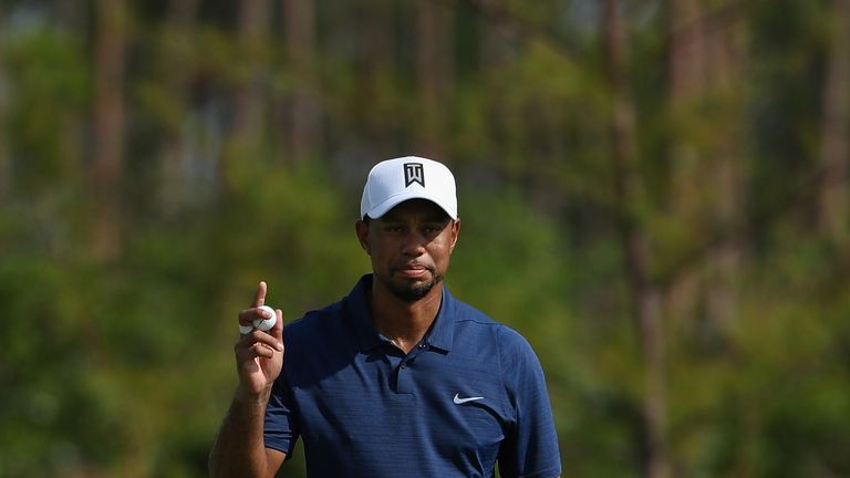 Tiger Woods acknowledges the crowd after tapping in for birdie at the 12th