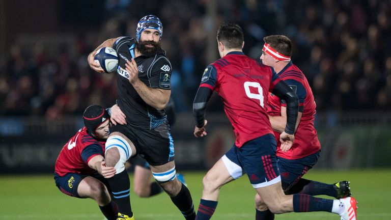 Josh Strauss is tackled by Munster's Tyler Bleyendaal (left)
