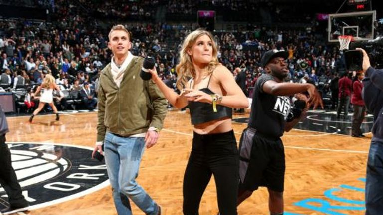 Bouchard throws shirts into the crowd at the NBA game, accompanied by Goehrke