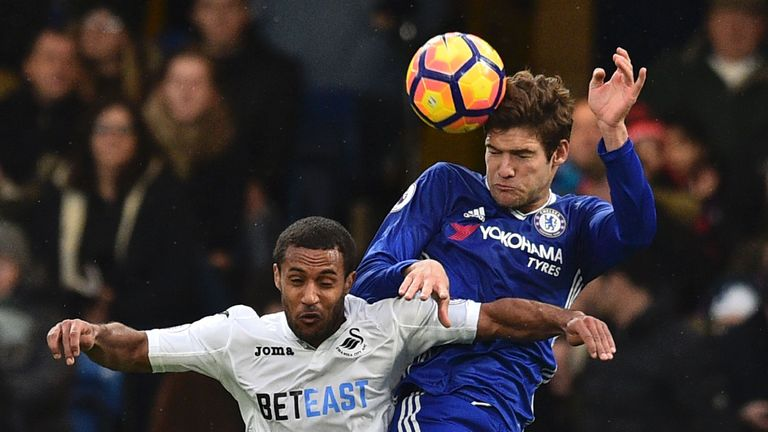 Chelsea's Spanish defender Marcos Alonso (R) beats Swansea City's English midfielder Wayne Routledge (L) in the air during the English Premier League footb
