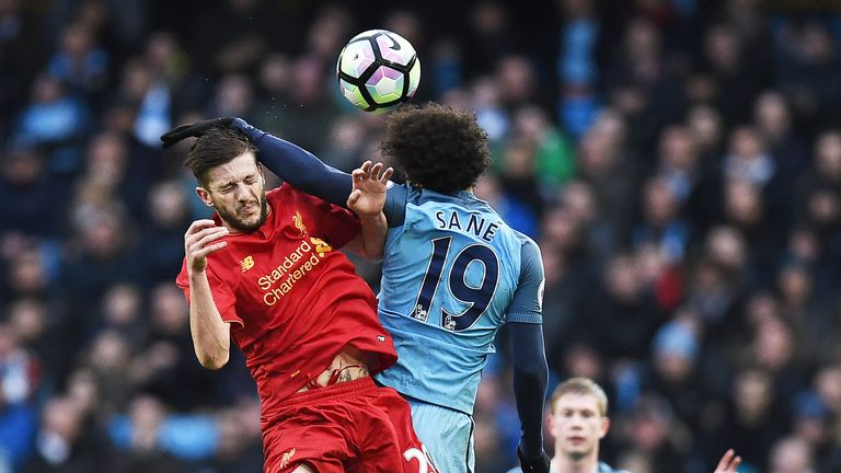 Adam Lallana competes with Leroy Sane for possession of the ball