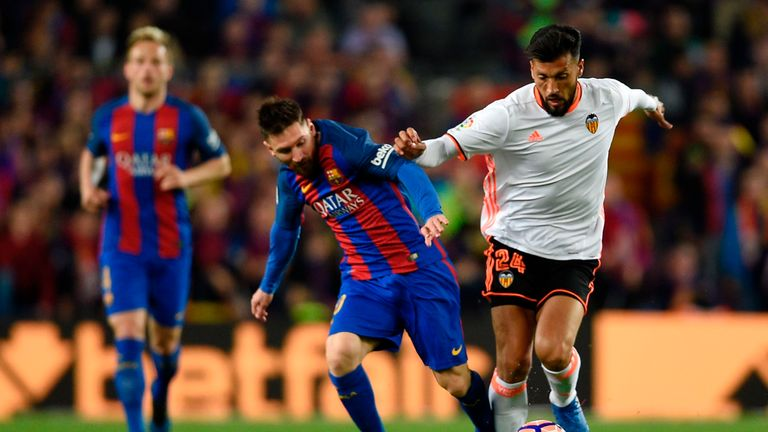 Lionel Messi (L) vies with Ezequiel Garay (R) during Barcelona's win over Valencia