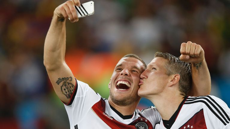 Bastian Schweinsteiger (R) and team-mate forward Lukas Podolski  take a 'selfie' after their 2014 World Cup win