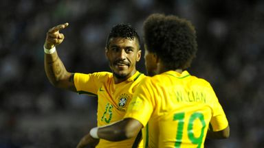 Brazil midfielder Paulinho (L) celebrates with team-mate Willian after scoring his second goal against Uruguay