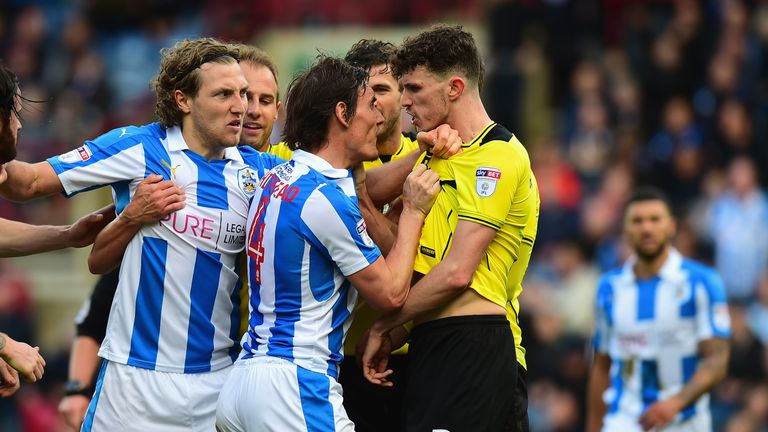 Dean Whitehead (centre) of Huddersfield Town confronts Tom Flanagan (R) of Burton Albion